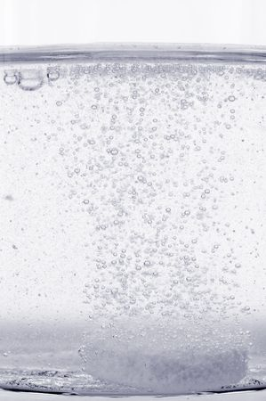 Pill dissolving in glass of water. Close-up. Shallow DOF. Duotone. photo