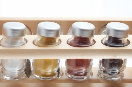 Cruet-stand with spice jars on white background.  photo