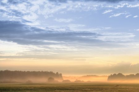 Fog over trees and meadow and blue sky with clouds. Early in the morning scene. Stock Photo