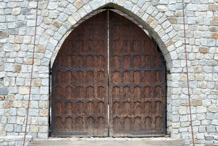 Old brown wooden gate in stone wall. photo