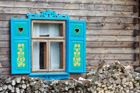 Opened window with decorative colorful shutters and logs below. photo