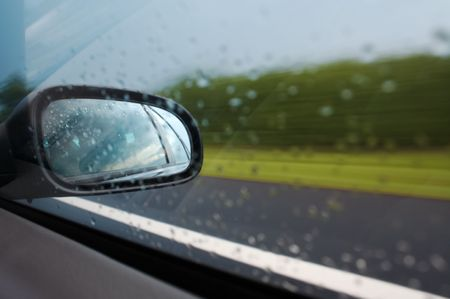 View through wet window at clouds in rear mirror with road background. photo