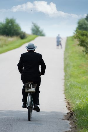 Old person in suit and hat riding a vintage bicycle. Stock Photo