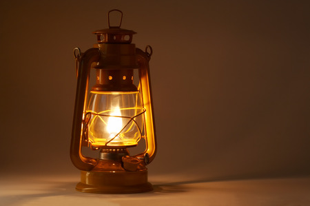 Old fashioned lantern in darkness. Light concept.
