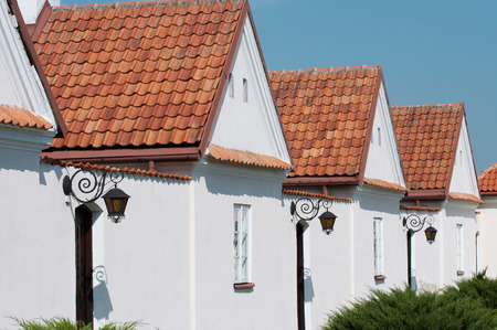 homeownership: White houses in a row, red roof top, blue sky.