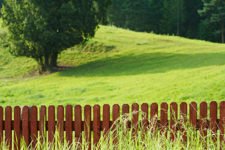 Red picket fence against green grass and tree. Focus on fence. Shallow DOF. Stock Photo - 1528272