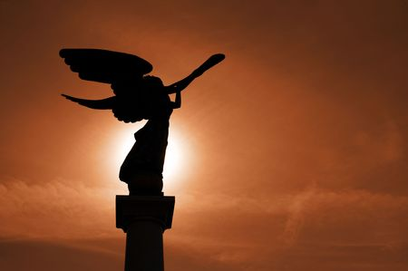 cornet: Silhouette of angel with cornet against sunset.