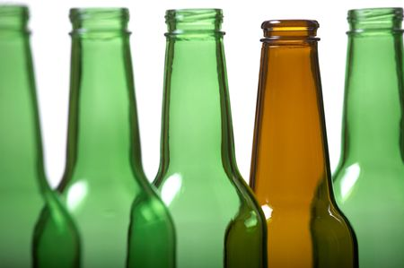 Brown beer bottle among green bottles. Concept of difference. photo