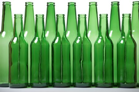 Small and high green beer bottles. Concept of equality. Shallow DOF. photo