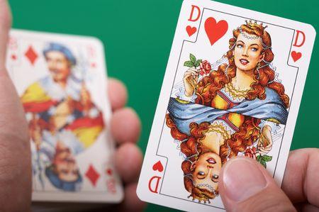 Hand revealing Queen of Hearts. Shallow DOF. Focus on Queen.