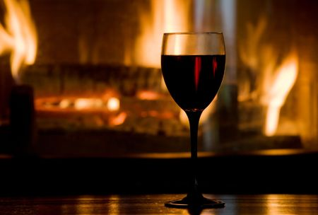 Wine glass on wooden table against blazing fireplace. Shallow DOF.