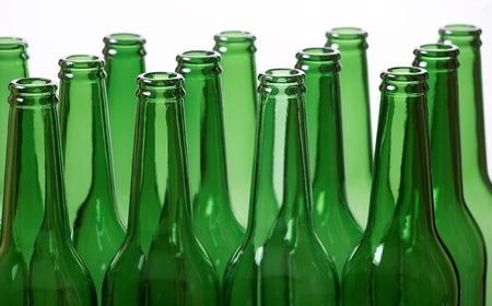 Group of green beer bottles against white. Shallow DOF. Focus on first row. photo