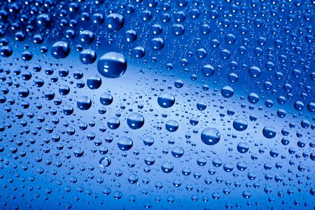 Water drops on blue background macro. Shallow DOF.