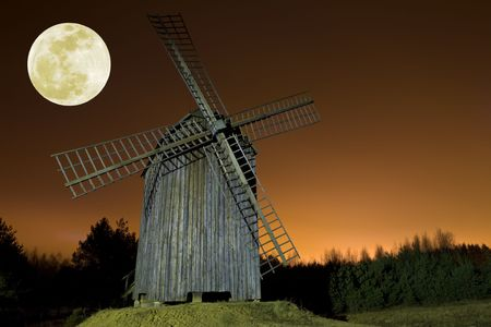 Old wooden windmill and moon. Night shot. Space for text. photo