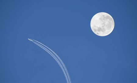 deflect: Aeroplane swerve and big moon against blue sky. Conceptual photo.