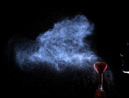 weightless: Cara silueta a soplar con pincel rojo en polvo. Polvo de nubes. Fondo negro.
