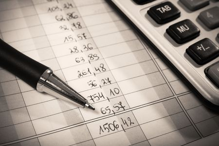 summation: Pen and calculator on financial document. Macro. Shallow DOF.