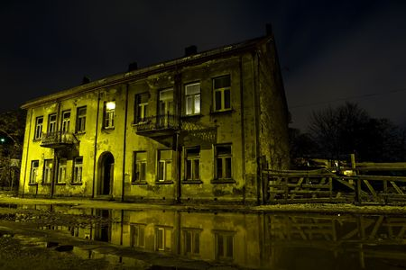 View of shabby building reflecting in water. Grunge background. Old construction. Night shot. Stock Photo