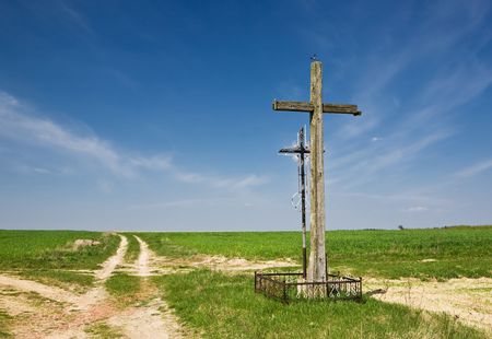Old wooden and metallic cross at country road. Green grass and blue sky. photo