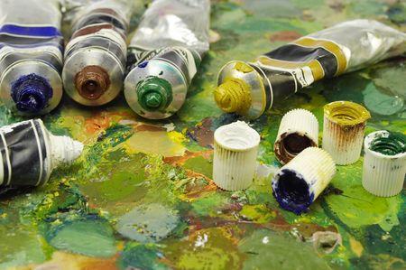 mass on painting palette. dye tubes lying among multicolour spots.