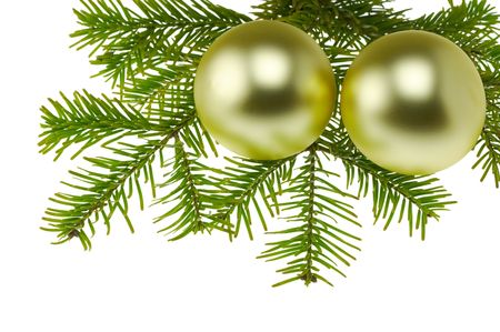two golden christmas ballsbaubles lying on green  Christmas wreath. Isolated on white. Stock Photo