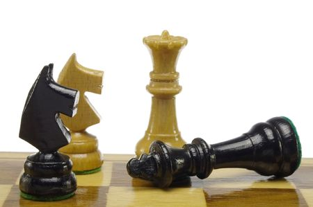 bad plan: Chess game - white queen with the black king lying on a board Stock Photo