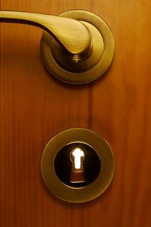 part of wooden door with metallic keyhole