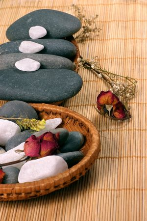 destress: Natural pebbles and dried rose petals on the rattan background. Suitable for spa and relaxation setting