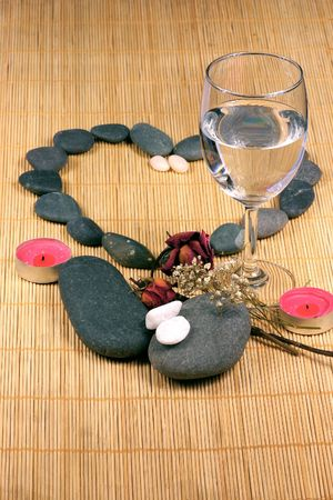 A heart, a glass, a couple of candle, natural pebbles and dried rose petals on the rattan background. Suitable for spa, romance and relaxation setting photo