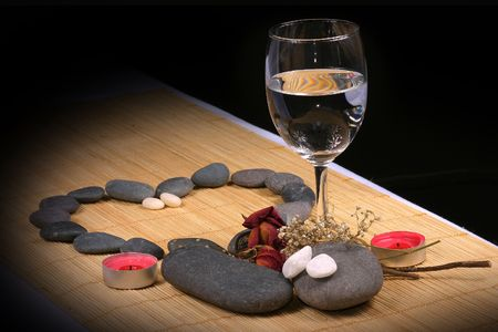 A hear, a glass, a couple of candle, natural pebbles and dried rose petals on the rattan background. Suitable for spa, romance and relaxation setting photo