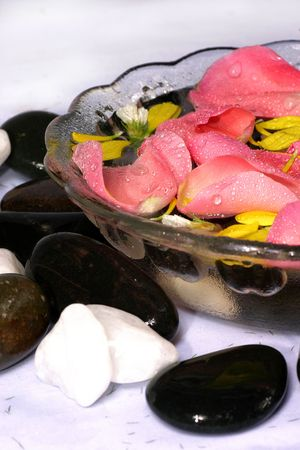 destress: Close up view of rose petals and natural pebble. Suitatble for spa and relaxation setting Stock Photo