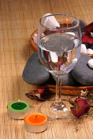 (A glass, a couple of candle, natural pebbles and dried rose petals on the rattan background. Suitable for spa and relaxation setting photo