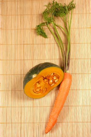 fresh pumpkin and carrot on the rattan background photo
