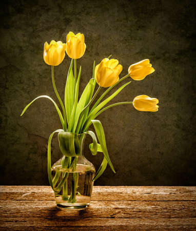 april flowers: Yellow tulips in glass vase with rustic wood background