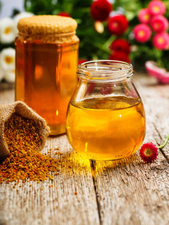 hive: Still life of jars of honey, pollen and flowers Stock Photo