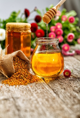 Still life of jars of honey, pollen and flowers photo