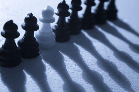 A single white pawn among black pawns.