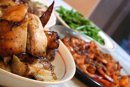 Un piatto di pollo arrosto diffusione sul tavolo da pranzo con gamberi e verdure in background.  Archivio Fotografico