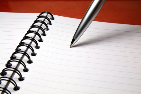 A silver ballpoint pen with its tip resting on a blank page of a notebook.