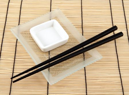 Sushi plate and chopsticks on bamboo mat photo