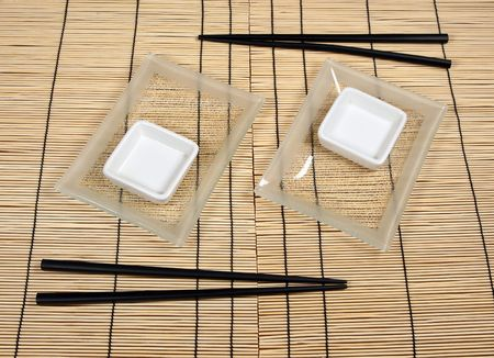 Sushi plates and chopsticks on bamboo mat photo