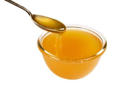 cuiller�e: la tasse et la cuiller�e de miel, disolement sur le blanc, chemin coupant ont inclus