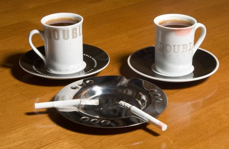 Two cups of coffee and two cigarettes on a table photo