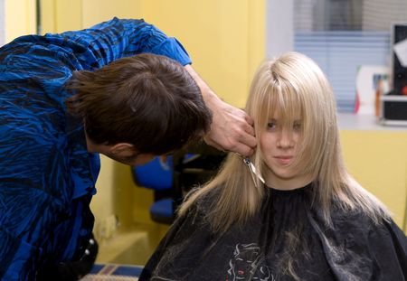 Barber makes a hair-dress to the young blonde Stock Photo - 643981