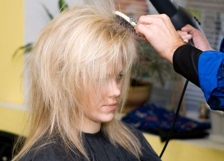 Barber makes a hair-dress to the young blonde photo
