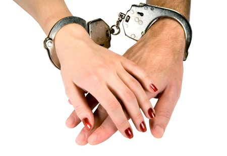 Hands of men and women in handcuffs, isolated on white photo