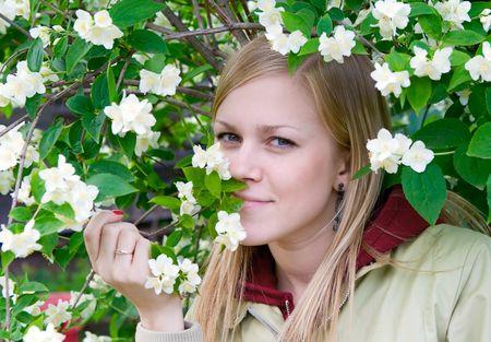 Young blonde at a bush of a jasmin