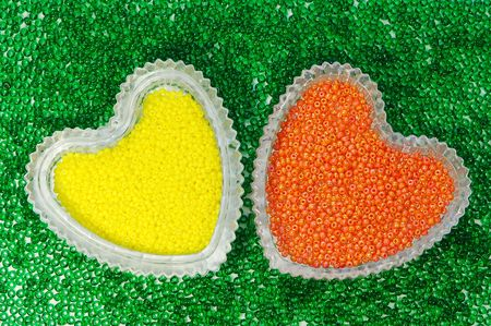 Multicolored plastic beads in heart-shaped crystal vases. Stock Photo