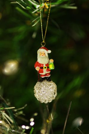 A Santa Claus decoration hanging on a christmas tree.