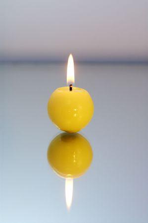 Runde gelb Kerze brennen auf eine reflektierende Oberfl�che. Lizenzfreie Bilder